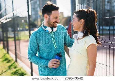 Handsome man and attractive woman talking and having fun time on court