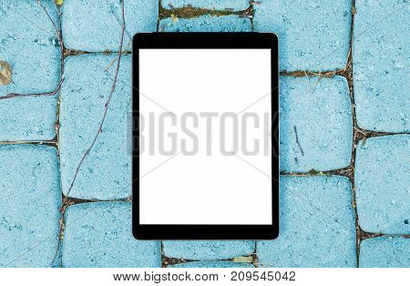 Tablet computer on grey stone blue background. Isolated white screen with copy space. Empty space for text. Empty blank screen.