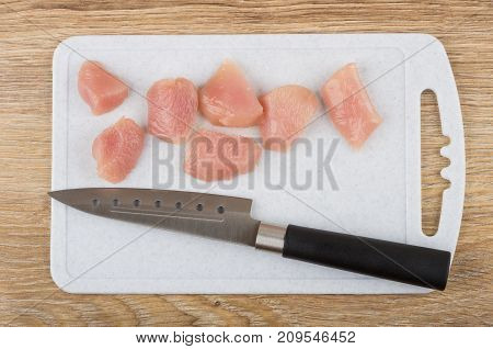 Pieces Of Raw Chicken Meat And Knife On Cutting Board