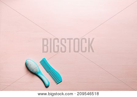 Two aquamarine hair comb crest brushes with handle for all types, isolated on pink copy space background. Minimalistic feminine flat lay.