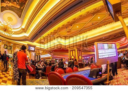 Macau, China - December 9, 2016: gamble table of card games at The Venetian Casino in Macau. Wide angle view with roof and game monitors.