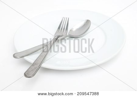 empty new ceramics plate with spoon and fork isolated on white background