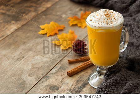 Pumpkin spiced latte on wooden table. Typica halloween drink