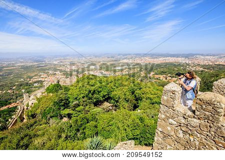 Photographer with stabilizer and professional camera takes photos at Sintra Valley from Castle of Moors. Moorish fortress is medieval castle and Unesco Heritage on top of a hill above Sintra, Portugal