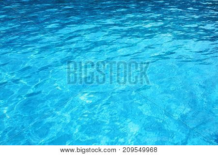 Swimming pool water background close up.  Blue swimming pool rippled water detail .