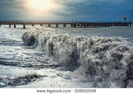 View of the pier at stormy evening time.