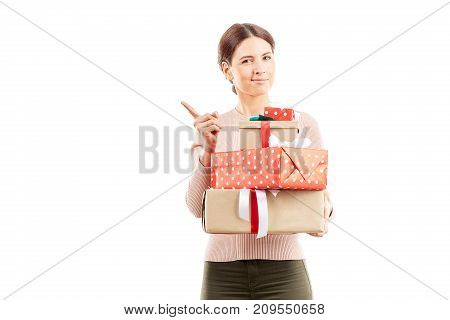 Portrait of young woman holding stack of Christmas gifts