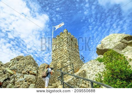 Photographer with stabilizer and camera takes video at Castle of Moors. Ancient flag of portugal on tower above Sintra, Lisbon District, Portugal. Unesco Heritage and popular landmark.