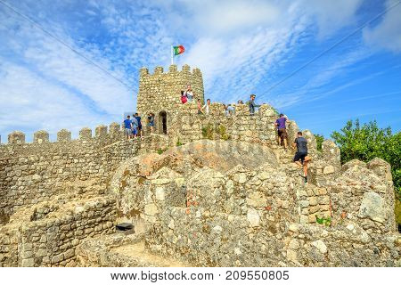 Sintra, Portugal - August 7, 2017: old wall and defensive tower of Castle of the Moors and Sintra valley, Lisbon District. People walk over defensive walls in one of Sintra's most popular attractions