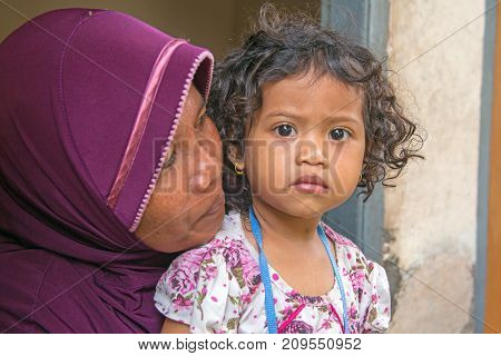 LOMBOK, INDONESIA - DECEMBER 30, 2016: Traditional indonesian mother with her young kid in Lombok Indonesia on 30th of december 2017