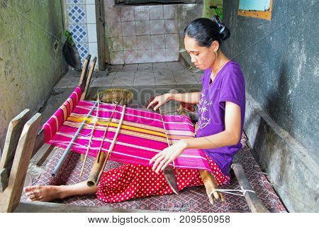 LOMBOK, INDONESIA - DECEMBER 30, 2016: Woman weaving on a loom in Lombok on 30th december 2016 in Indonesia