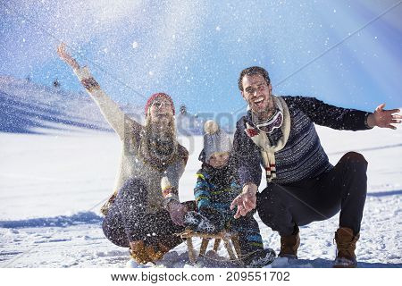 the happy family rides the sledge in the winter wood, cheerful winter entertainments, everything is covered with snow around.