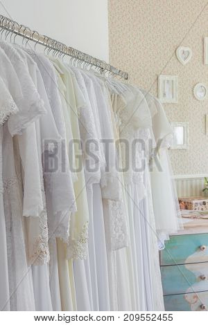 Interior of bridal salon. Beautiful wedding dress on a hangers. In vintage style