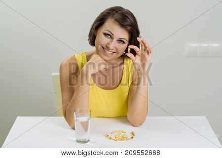 Smiling Woman Taking Fish Oil Pill Omega-3.  Vitamin D, E, A Fish Oil Capsules. Diet. Nutrition. Hea