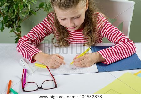 A  Junior Schoolgirl With Glasses Writes Something With Her Left Hand In The Notebook And Sits At Th