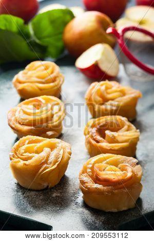 Apple Rose mini tarts with icing sugar on the stone cutting board.