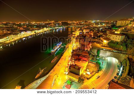 Aerial view of Oporto skyline and Ribeira Waterfront from Dom Luis I Bridge at night. Picturesque urban cityscape of Porto in Portugal.Rabelo and tourist boats on Douro River. Porto colorful nightlife