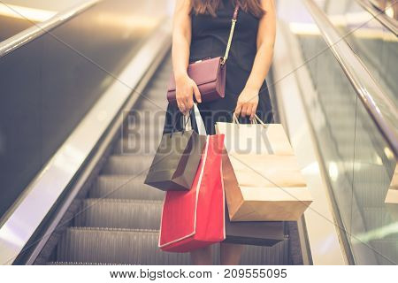 Young woman carry many colorful shopping bags