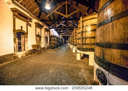 Porto, Portugal - August 13, 2017: cellar with traditional aged wooden wine barrels, big and small. Inside of Ferreira Winery in Vila Nova de Gaia, one of the most popular wine tasting tours.