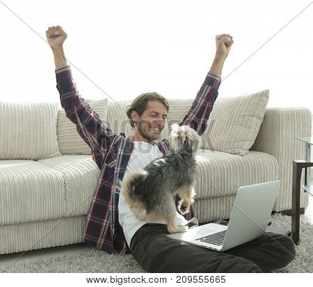 happy guy with his dog sitting in a spacious living room