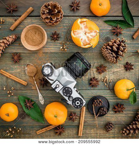 Christmas still life with old retro camera, cinnamon and mandarin. Flat lay. Top view