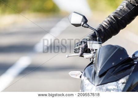 Black, a sport motorcycle close-up costs only on the road with its gas owner, brake close-up
