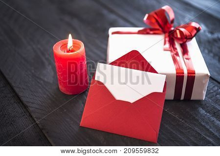Red empty envelope leaned against a stylishly wrapped gift tied with red ribbon and bow near a lit candle on an old wooden table.