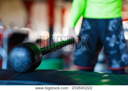 Close-up of a hammer lying on a tire in the gym. In the background a man in green holds a hammer. The concept of sport.