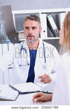 Mature male doctor hold in arm and look at xray photography discussing it with female patient portrait. Bone disease exam medic assistance cancer test healthy lifestyle hospital practice concept