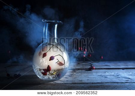 bottle with glowing smoke and rose hips inside on a rustic wooden table against a dark blue background mysterious halloween alchemy still life with copy space selected focus narrow depth of field