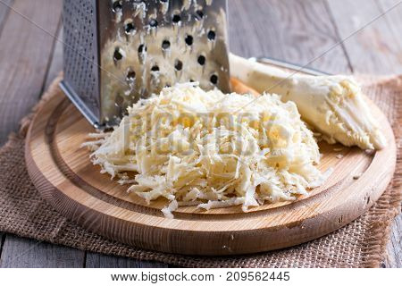 Grated parsnip on cutting board on a wooden table