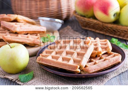 Waffle with apples on a wooden table. Vintage style