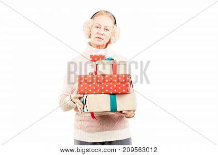 Portrait of senior woman in earmuffs holding heap of Christmas gifts