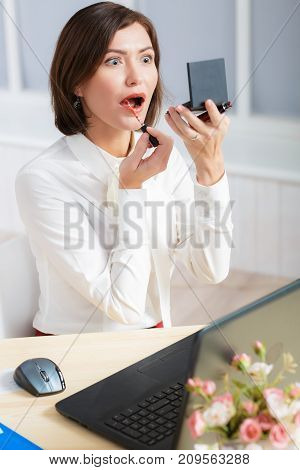 attractive business woman doing makeup at the office