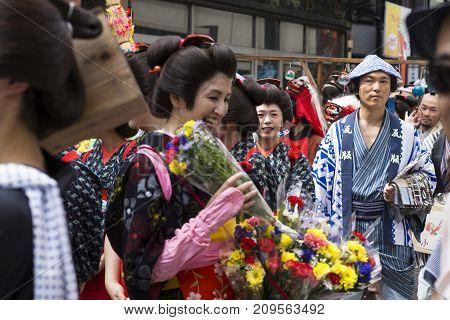 Tokyo, Japan - September 24 2017: Woman Giving Flowers To The Visitors At Shinagawa Shukuba Matsuri