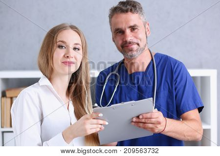 Smiling handsome doctor communicate with patient holding silver pen and showing pad. Physical agreement signature disease prevention consent sign 911 prescribe remedy healthy lifestyle concept