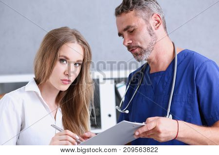 Handsome mature doctor offer pad sign with silver pen portrait. Physical agreement form signature disease prevention ward round reception consent contract prescribe remedy healthy lifestyle concept