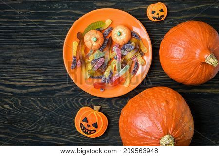 Halloween holiday background with pumpkins candy and cookies. View from above.