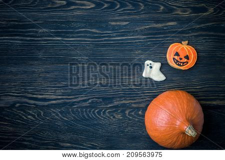 Halloween holiday background with pumpkins and cookies. View from above.