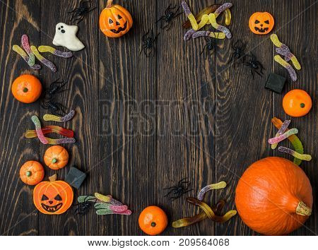 Halloween holiday background with pumpkins candy and spiders. View from above.