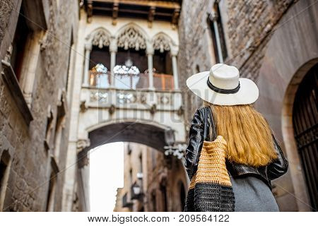 Young woman tourist looking on the famous bridge of Sighs in the old town of Barcelona city
