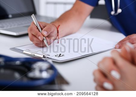 Male doctor hand write prescription at office worktable using silver pen. Panacea life save prescribing antidepressant legal drug store vitamin aid ward round give or take potion concept