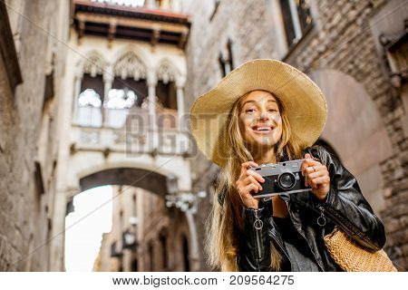 Young woman tourist in hat standing with photo camera in front of the famous bridge of sighs in Barcelona old town