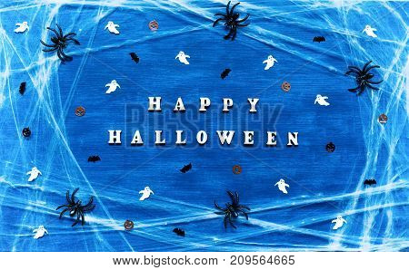 Halloween background. Happy Halloween letters with spider web spiders and Halloween decorations on the dark blue background. Festive Halloween background with Happy Halloween concept. Halloween still life