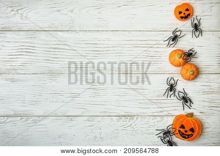 Halloween holiday background with pumpkin cookies and spiders. View from above.