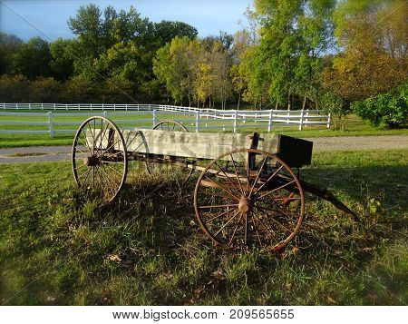 An old wooden wagon creates a nostalgic display in a farmer's field on an early autumn evening.