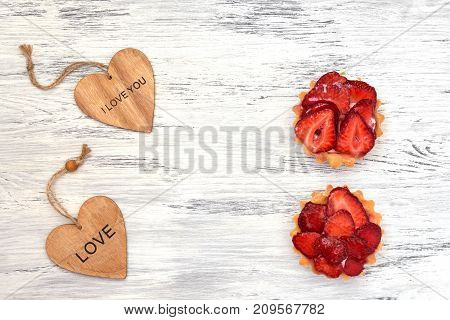 A cake with strawberries and a wooden heart on a white painted surface. Valentine's Day