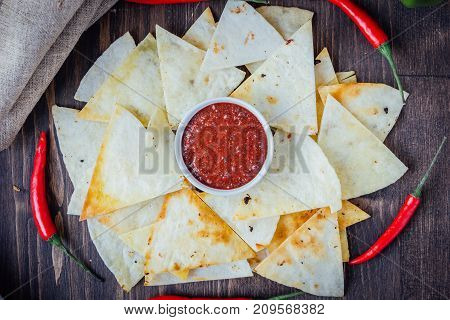 Hot salsa dip over the hip of nachos chips - organic home made sauce