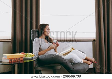 Beautiful Young Woman At Home Sitting On Modern Chair In Front Of Window, Relaxing In Her Living Roo