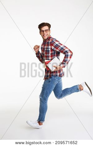 Full length portrait of a smiling young male student with books running and looking at camera isolated over white background